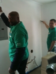 Bridge Communities volunteers paint the laundry room during Comcast Cares Day