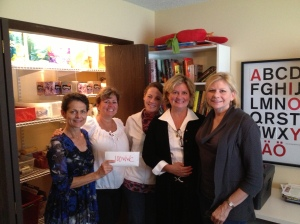 Vicky Joseph of Bridge Communities accepts a $10,500 donation from 100+ Women Who Care.